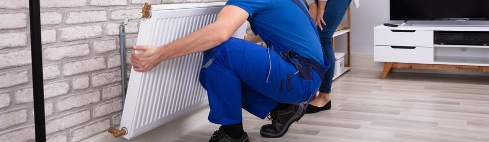 Technician performing heater repair in home